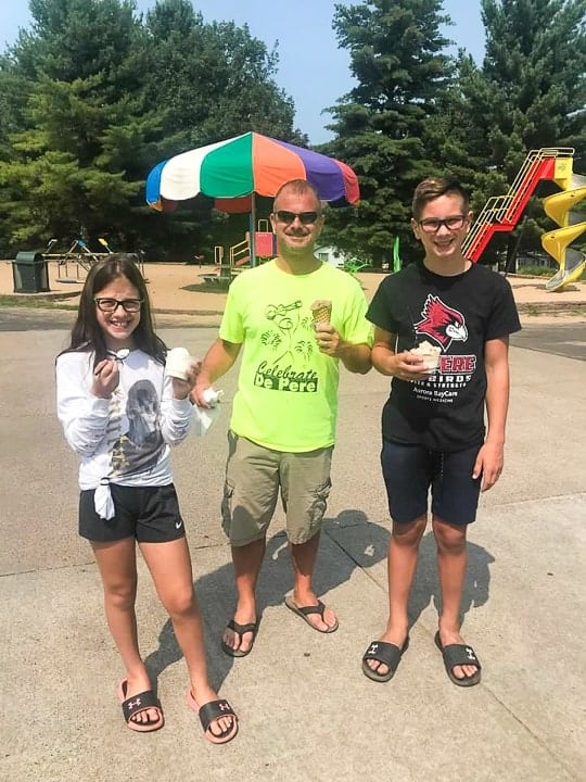 best camping in wisconsin includes ice cream! showing a girl, boy and their dad enjoying a cone by the park at evergreen campground in wi.