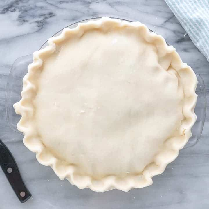 Top crust is added to the easy chicken pot pie and edges are pinched together.