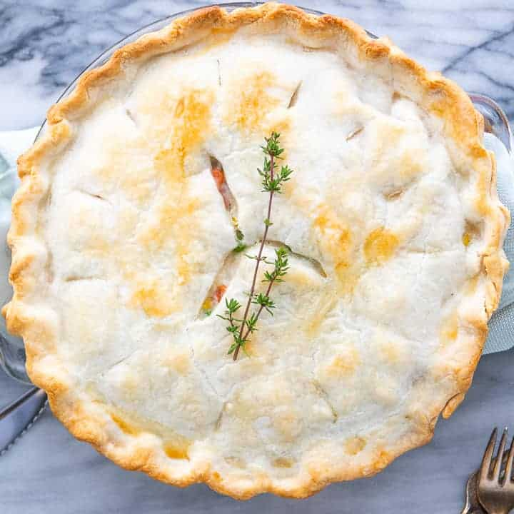 Creamy easy chicken pot pie shown baked with thyme leaves on top of the pie on a white marble surface.