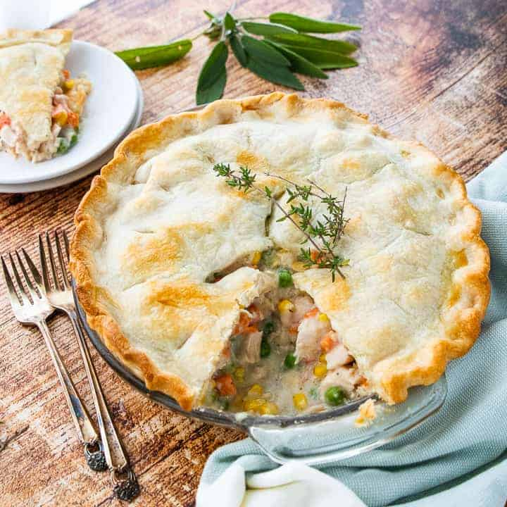 Creamy chicken pot pie recipe showing a slice out of the pie with the slice on a plate in the background next to 2 forks.