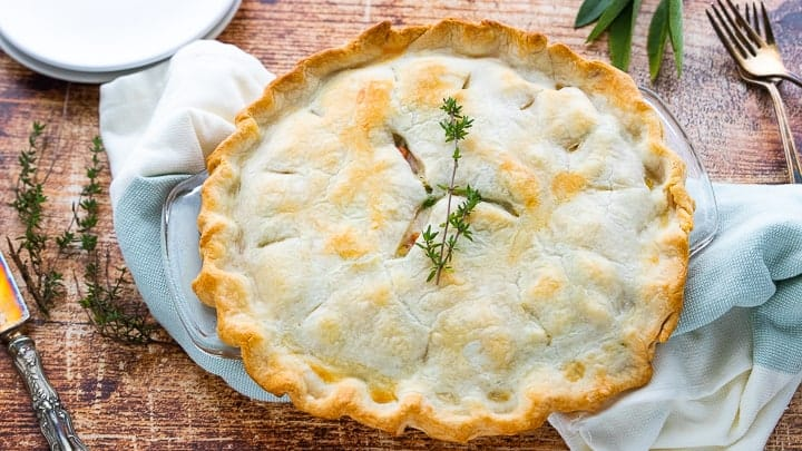 an old fashioned pot pie shown on a wooden surface that's baked but not yet sliced.
