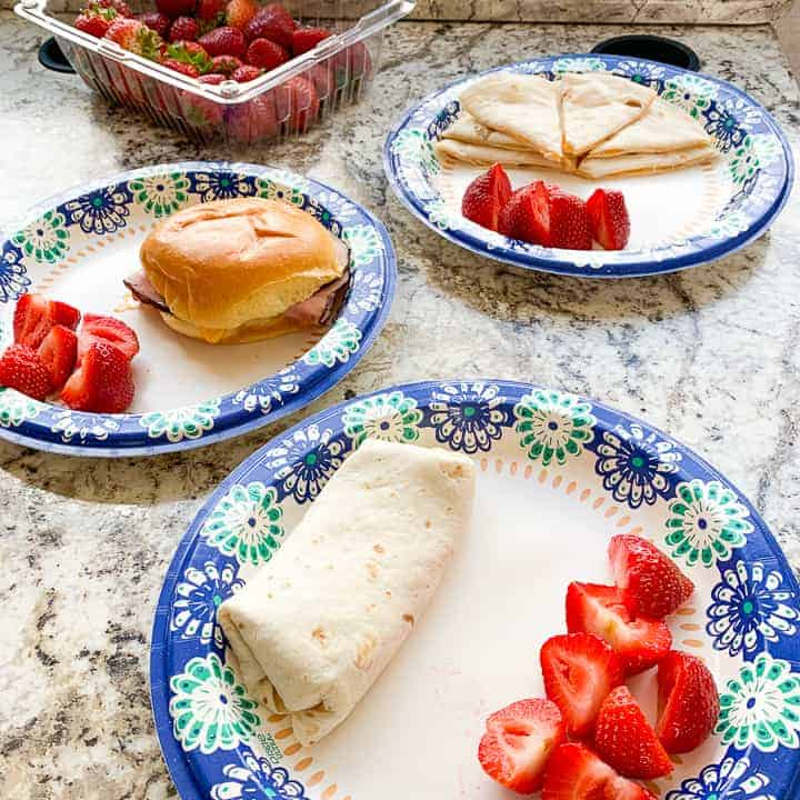 rv meals including a ham sandwich, quesadilla, and a burrito on paper plates with strawberries in an RV