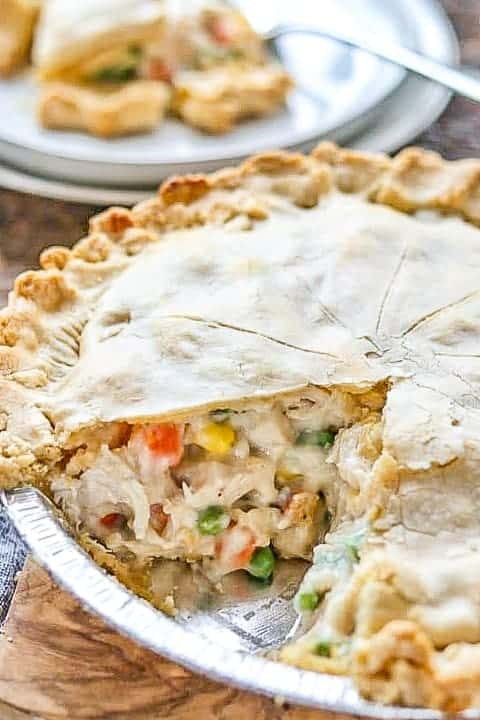 creamy Chicken pot pie with pie crusts shown up close in a pie pan with on slice removed showing the chicken and vegetables inside the easy chicken pot pie recipe.