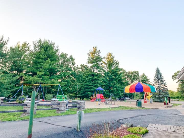 best camping in wisconsin showcasing a playground next to the woods with a twisty slide.