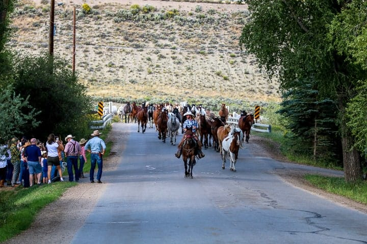Dude ranch Colorado, showing individuals riding horses down a highway with other individuals standing on the side of the highway viewing the horses with the Colorado scenery surrounding.