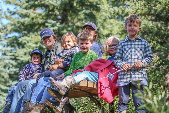 Kids being shown sitting on a bench, smiling and enjoying the kid program at a family dude ranch in Colorado.