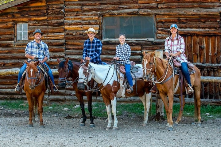 A family of four being shown on a family dude ranch in Colorado sitting on horses with a log cabin behind.