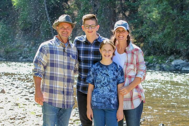 A family of four standing along the Colorado River while enjoying a Colorado vacation on a family dude ranch