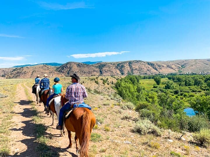 A family of four enjoying a horseback ride along a dirt path in Colorado headed back to the Colorado ranch to enjoy a homemade breakfast.