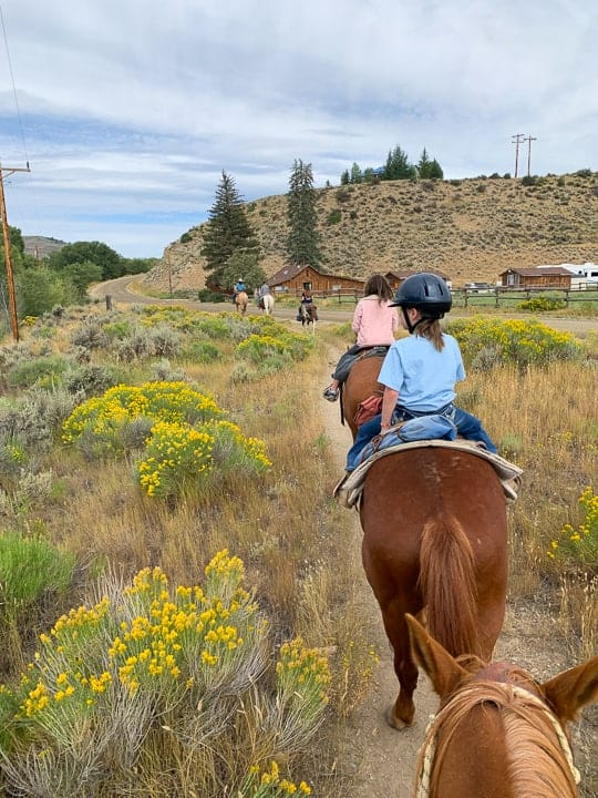 Kids riding horses enjoying a ride along a dirt path in Colorado headed to visit a local town next to a family dude ranch.