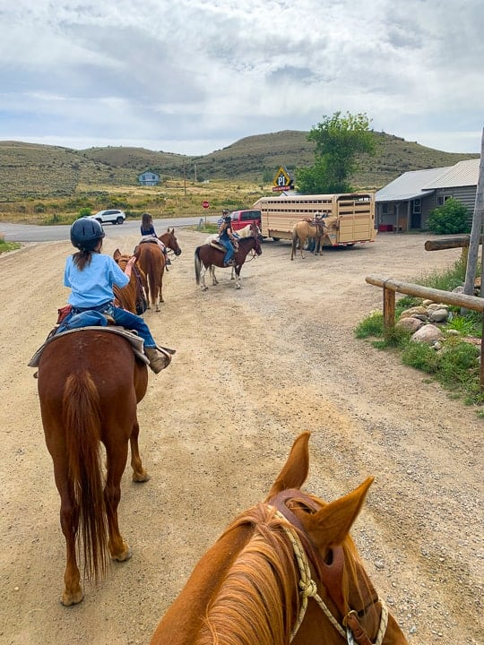 Kids taking a loping or walking ride on horses at a family dude ranch with the Colorado scenery surrounding.