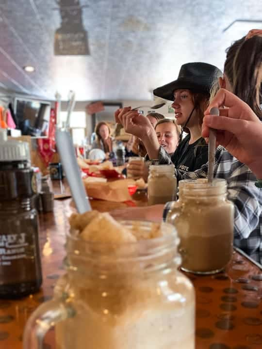 Kids enjoying root beer floats at a local restaurant in Colorado while laughing and sharing memories of their Colorado ranch vacations.
