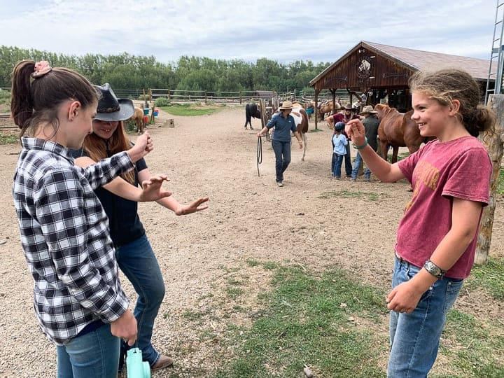 Three young girls being shown standing outside playing a game with a horse barn on a dude ranch Colorado.