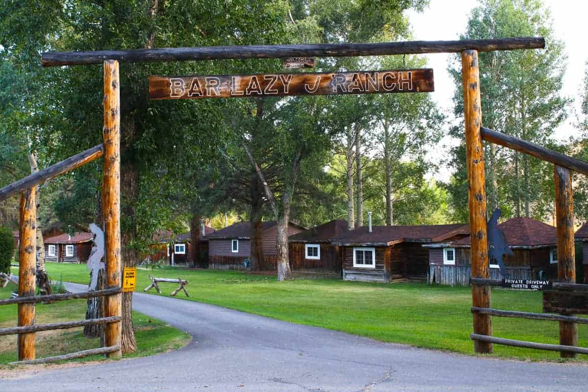 The entrance for Bar Lazy J Ranch, a Colorado ranch, with cabins in the background.
