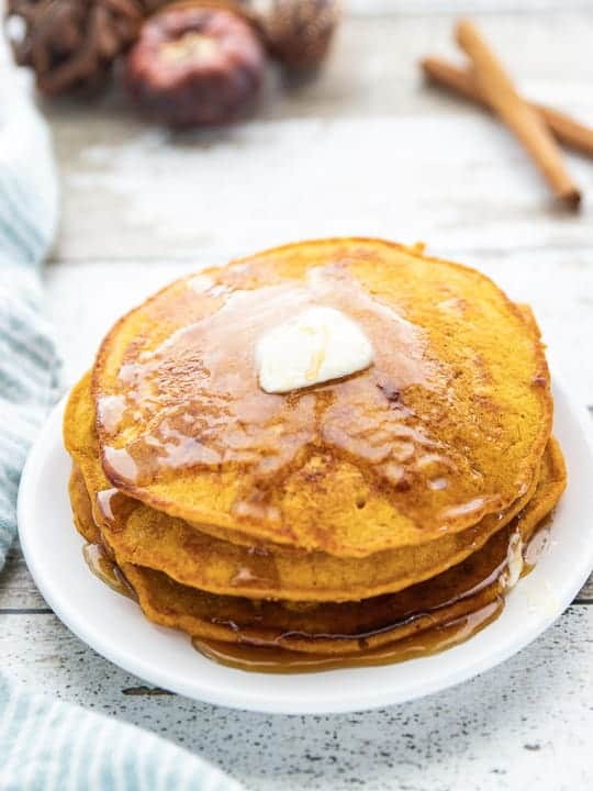Healthy Pumpkin Pancakes, a pumpkin spice pancake recipe, showing a stack of pancakes with a pat of butter and drizzled maple syrup on the top all on a white plate.