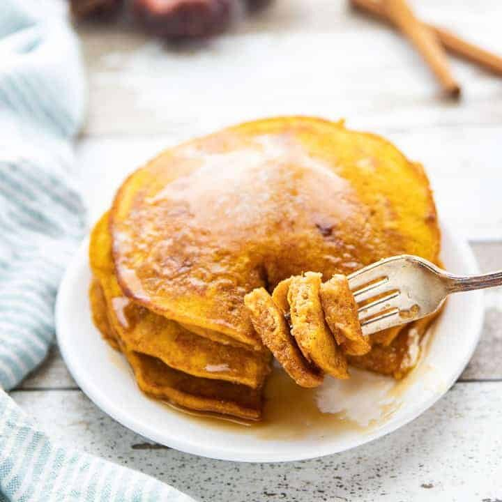 three pumpkin pancakes stacked on a white plate with syrup drizzled on top and a fork taking a bite out.