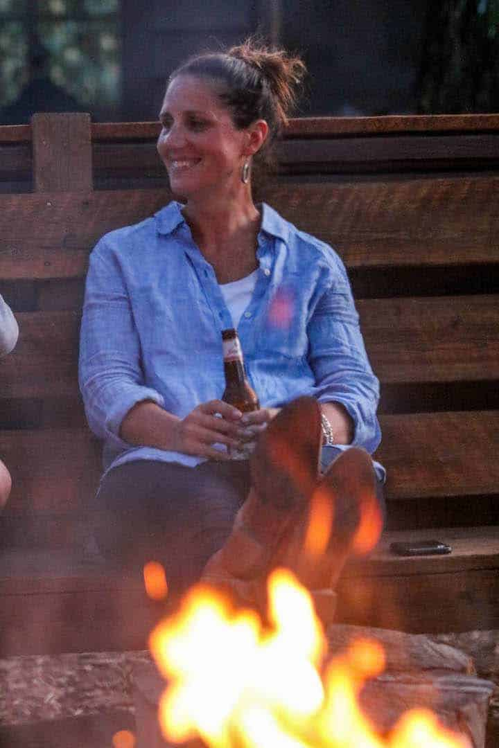 A women being shown sitting next to a campfire on a Colorado ranch vacation holding a beer and smiling.