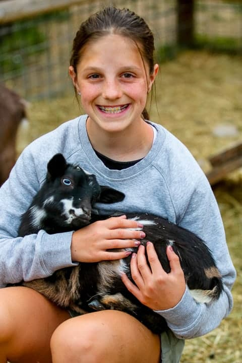 family ranch vacation showing a girl holding black and white baby goat.