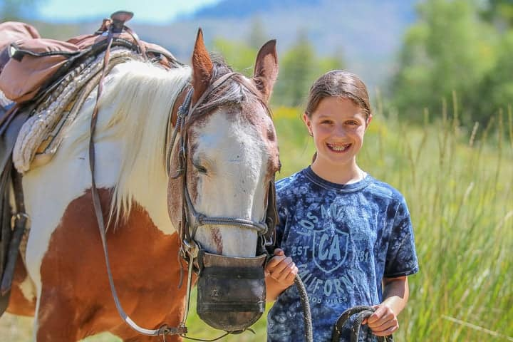 family ranch vacation showing a young girl in a blue t-shirt holding the reins of a brown horse both standing in a pasture on a Colorado dude ranch.