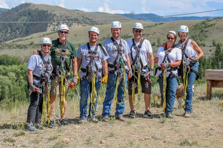 family ranch vacation showing a zipline over 1500ft with ranch visitors geared up for an eventful day on the ranch.