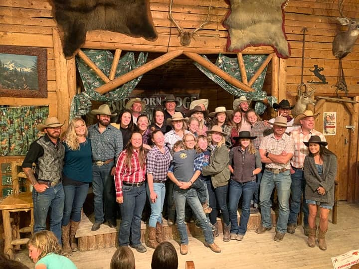 The ranchers being shown after a fine dining experience in a lodge on the dude ranch.