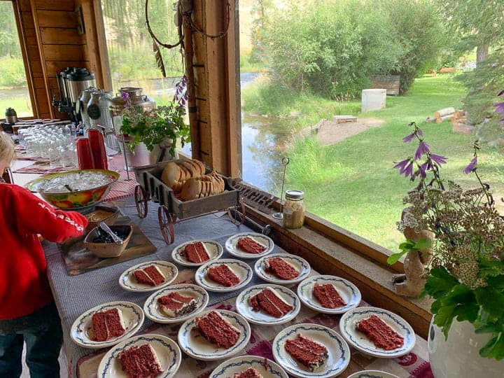 Slices of red velvet cake plated on white plates set on a long table with other desserts.