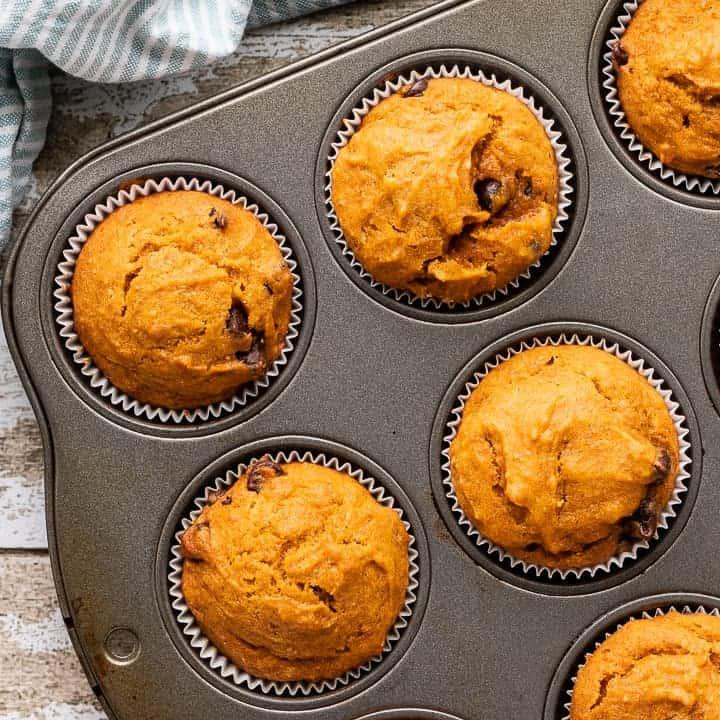 Chocolate Chip Pumpkin Muffins, a Pumpkin Chocolate Chip Muffins recipe, showing muffins in liners baked in a muffin tin.