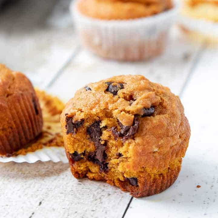 Chocolate Chip Pumpkin Muffins, a Pumpkin Chocolate Chip Muffins recipe, showing muffins on top of a wooden surface with a bite missing from one muffin.