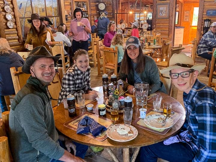 A family of four being shown sitting at a table eating a meal while enjoying an all-inclusive dude ranch vacation in Colorado.