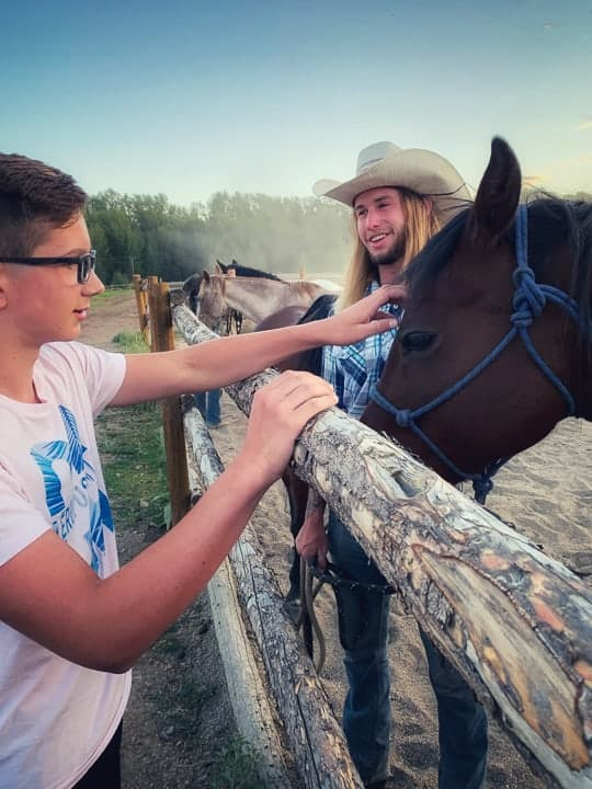 A young boy being shown petting a dark brown horse being held by a older boy on a dude ranch in Colorado.