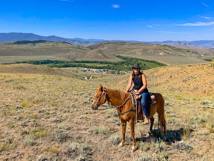 A women riding a brown horse in Colorado on a dirt path with the Colorado scenery surrounding.