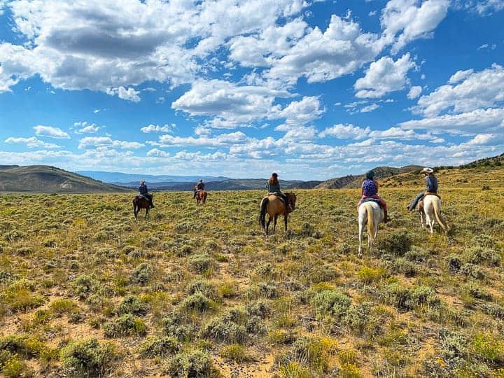 The ranch enjoying a horseback ride and views of the Byer's Canyon while on vacation at a family dude ranch in Colorado.