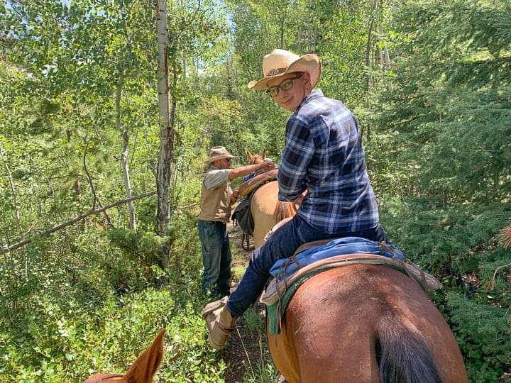 A teen boy in a blue flannel shirt riding a brown horse through a wooded area along a dirt path enjoying the Colorado scenery