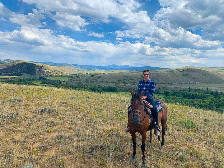 A young boy being shown on a dark brown horse enjoying the riding program at a family dude ranch in Colorado while on vacation.