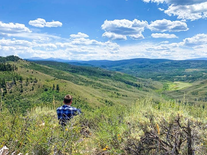 A teen boy enjoying the Colorado scenery while sitting on a mountain in Colorado while on vacation at a family dude ranch.