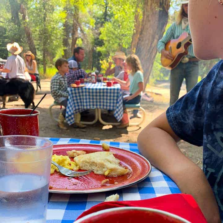Breakfast in the woods eaten on picnic tables with a cowboy playing the guitar.