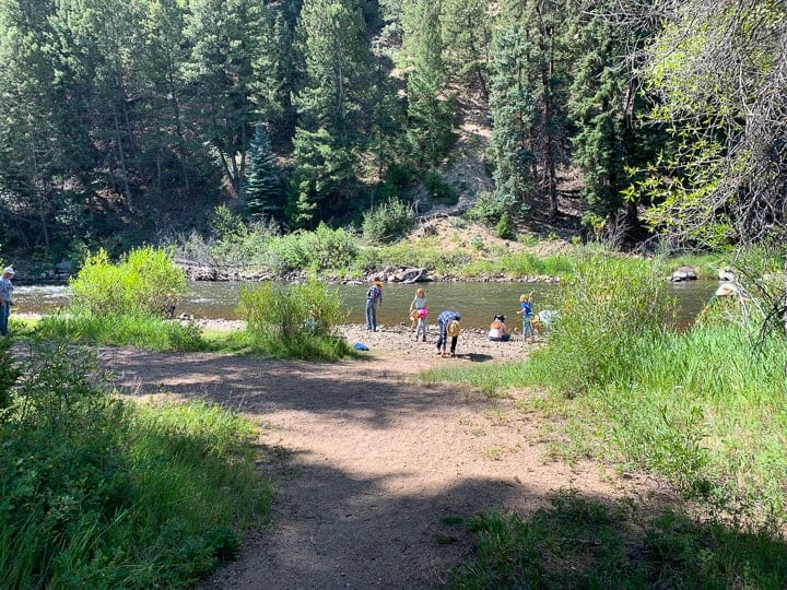 family ranch vacation, kids playing by the Colorado River, kids skipping stones along the river after a campfire breakfast