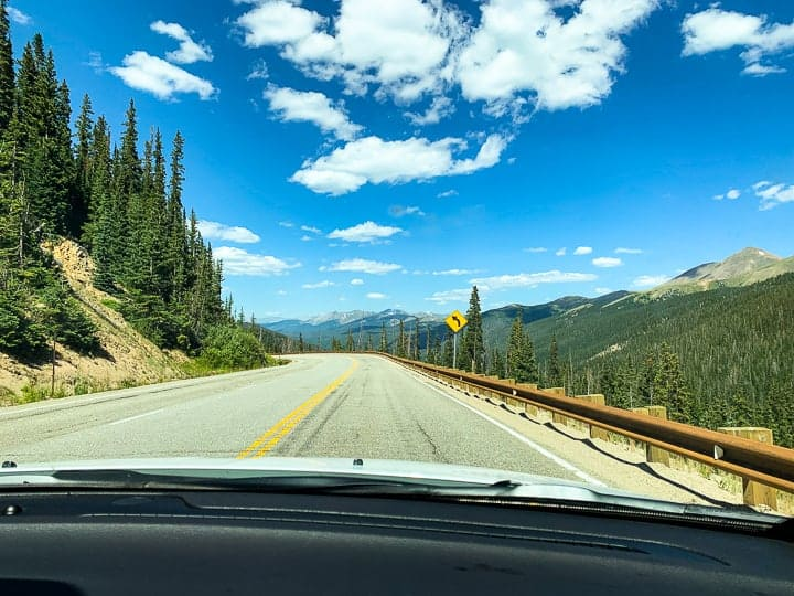 A car being shown driving down a highway from a passenger's view with the Colorado scenery surrounding the car headed to a family dude ranch.