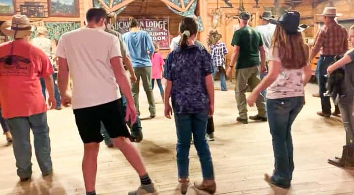 The entire ranch participating in line dancing to learn a few moves before heading home from their Colorado vacation at a dude ranch.