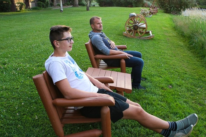 A father and son being shown enjoying Colorado ranch vacations by sitting in two wooden chairs with a wooden table between the chairs all placed on the grass at a dude ranch.