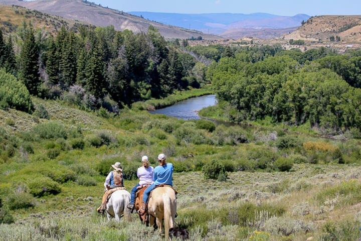 Riders headed to the water for a day of fly fishing while enjoying their stay at a family dude ranch.