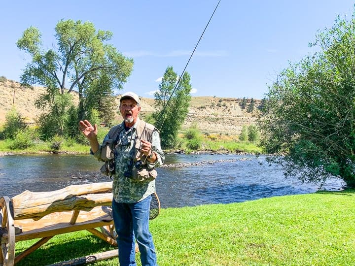 A man holding a fishing pole for a day of fly fishing next to a family dude ranch in Colorado.