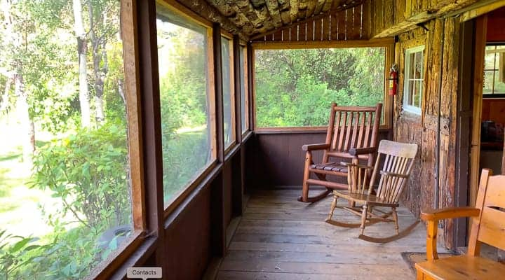 Rocking chairs on a porch of a log cabin at a family dude ranch in Colorado.