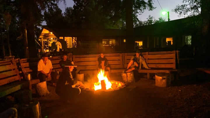 Ranchers enjoying nightly skits and entertainment around the bonfire on the dude ranch.