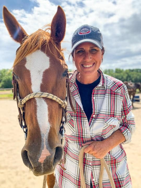 A women in a red flannel shirt holding the reins of a brown horse being shown standing on a family dude ranch after enjoying Colorado ranch vacations.