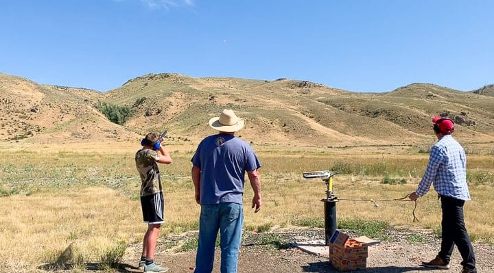Visitors of a family dude ranch in Colorado enjoying the local shooting range and the Colorado scenery.
