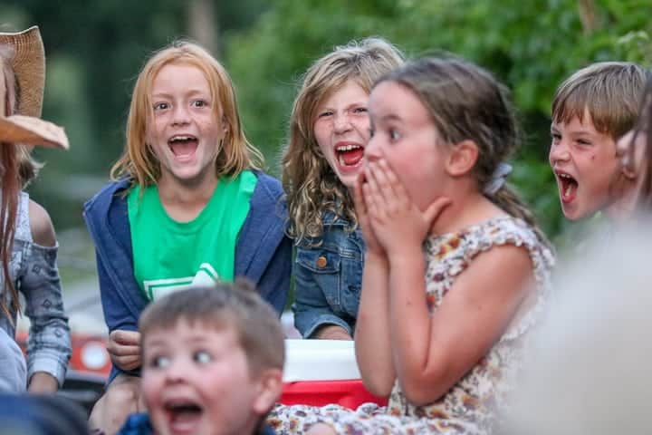 Laughing and smiling kids being shown on a family dude ranch enjoying the kid program.
