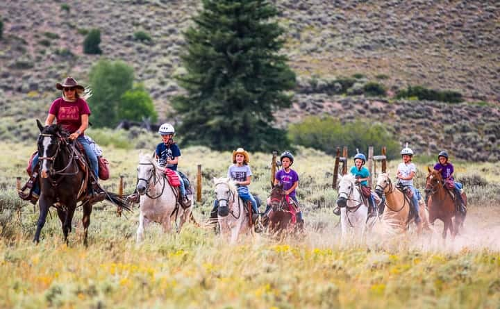 Kids being shown riding horses and being led by an adult rider as they all travel along a dirt path in Colorado headed back to a dude ranch with the Colorado scenery surrounding.