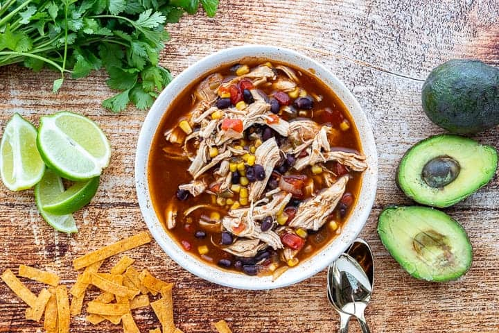 Instant Pot Chicken Tortilla Soup, an instant pot tortilla soup recipe, showing soup in a white bowl on a wooden surface with an avocado, tortilla strips, fresh limes and a spoon surrounding the bowl on the wooden surface.