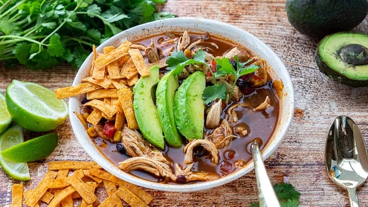 Instant Pot Chicken Tortilla Soup, an instant pot tortilla soup recipe, showing a white bowl filled with soup topped with avocado slices with a spoon in the bowl all on top of a wooden surface.